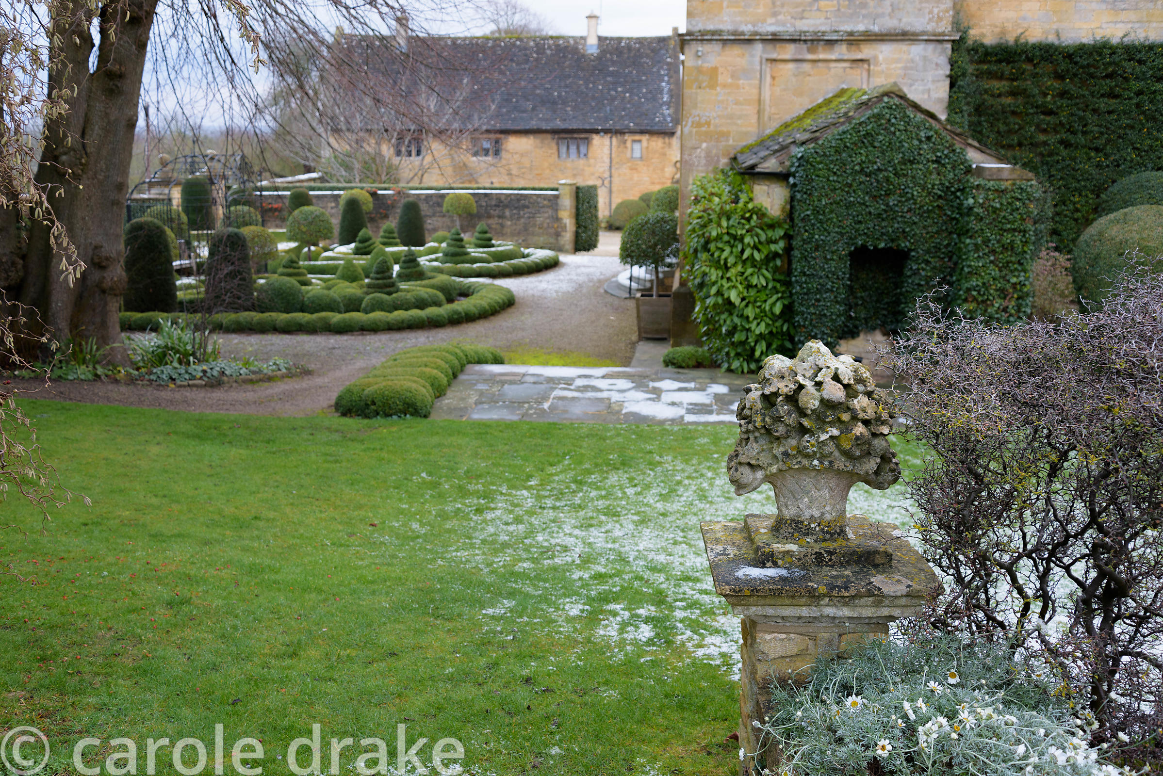 Bourton House in the Cotswolds in January with a light dusting of snow. A corokia and stone cornucopia frame a view towards t...