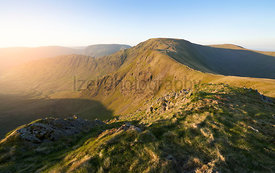 The warm morning glow of sunrise over the summit of High Street with Harter Fell to the left and Thornthwaite to the right fr...