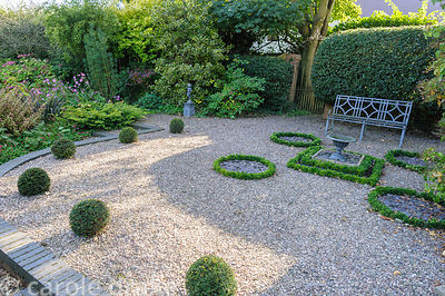 Topiary garden near the house with young yew spheres and Euonymus japonicus 'Microphyllus' as replacements for diseased box p...