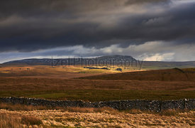 Storm clouds and sunshine over the Three Peaks Summit of Pen-y-g
