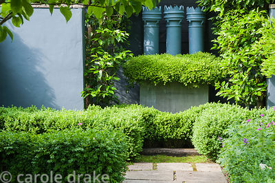 Three grey painted chimney pots with a skirt of small leaved box, Buxus microphylla, in a steel container. Tony Ridler's gard...