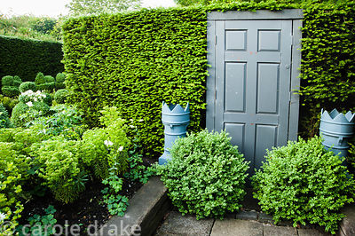 False grey door set into the yew hedge, framed by grey painted flower pots and loosely clipped box. Tony Ridler's garden, Swa...
