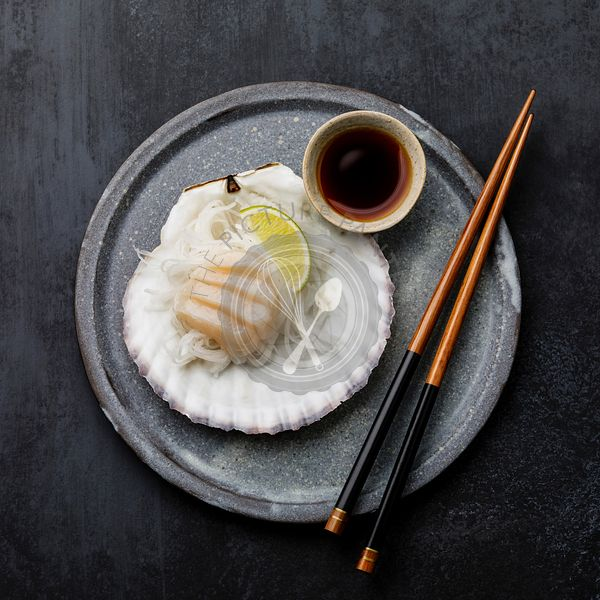 Live scallop sashimi on shell with daikon, lime and soy sauce on dark background