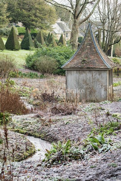 Stream running through the bog garden past a wooden summerhouse at the Old Rectory, Netherbury in January