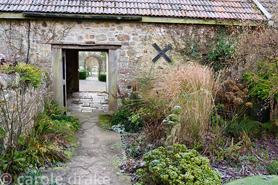 Stone path leads between borders of ferns, grasses, roses and hydrangeas and through an old barn towards an arch framing the ...