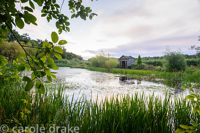 Wooden hut beside a pond at Broadwoodside, Gifford in September, modelled on the temple in the stumpery at Highgrove designed...