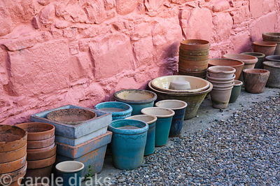 A collection of cleaned empty pots beside the pink wall of the house.
