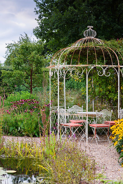 Metal gazebo beside a naturalistic pond in a garden in rural Nottinghamshire in September, with echinaceas, rudbeckias and Ac...