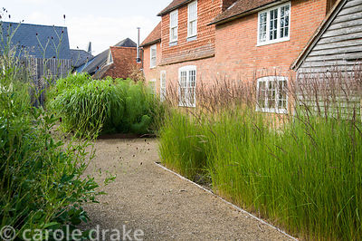 The front garden was designed by Christopher Bradley-Hole on a grid pattern, with tall grasses and subtle flowering perennial...