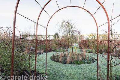 Formal flower garden with clipped box and steel obelisks and tunnels as plant supports at Ellicar Gardens, Notts in winter
