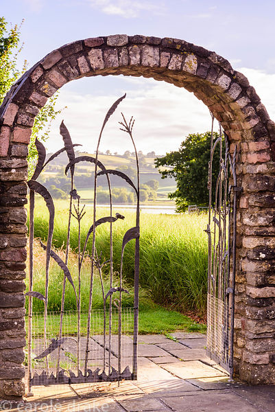 Decorative iron work gate picturing grasses and butterflies, framing a view through to Blagdon Lake and the surrounding count...