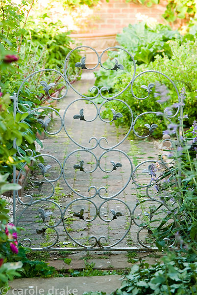 Decorative metal gates are a feature throughout the garden, here connecting the walled kitchen garden with the patio outside ...