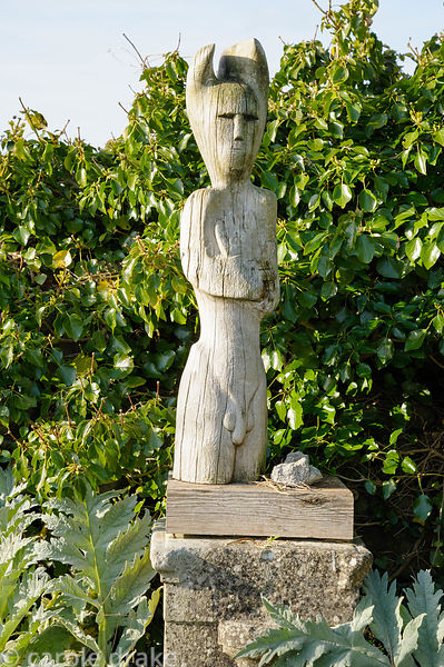 Carving of Cernunnos, the Celtic God of the Other World in yew wood by John Cleal in the kitchen garden, with the new leaves ...