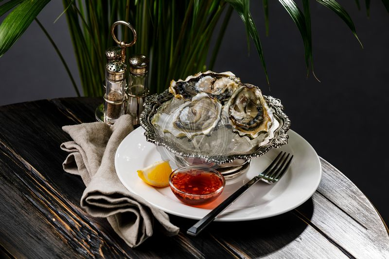 Fresh Oysters on ice in silver bowl and sauce on black wooden table