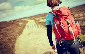 A closeup view of a female hiker walking along a trail on the moors with a red backpack on a sunny autumn day in Blanchland, ...