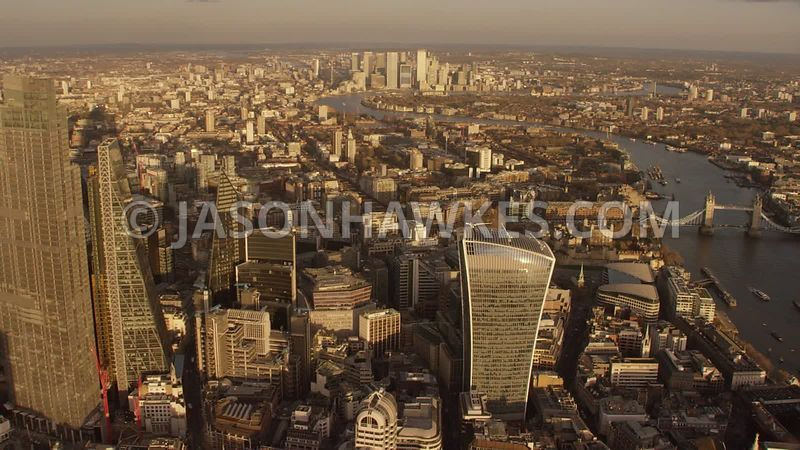 Aerial footage of the City of London, 22 Bishopsgate, Bank, 20 Fenchurch St, River Thames at sunset, London.