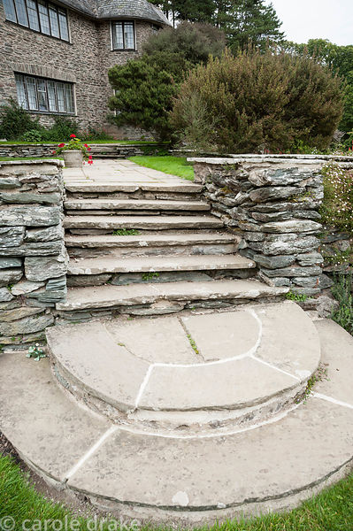 Stone steps leading up to the terrace beside the Arts and Crafts house. Coleton Fishacre, Kingswear, Devon, UK