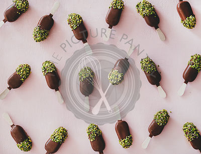 Chocolate glazed ice cream pops with pistachio icing pattern