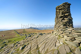 The rocky summit cairn of Thornthawite, the beacon, with perfect blue skies over the Lake District.