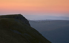 A distant hiker on the rocky summit of Kidsty Pike at sunrise from the summit of Rampsgill Head in the Lake District UK.
