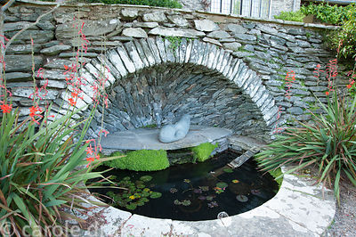 Upper concave pool on terracing in front of the house, designed by Oswald Milne, with stone otter by Bridget McCrum. Coleton ...