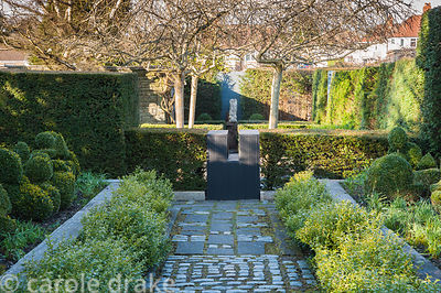 A path of paving slabs and stone setts is bordered by Christmas box, Sarcococca confusa, raised beds containing box topiary s...