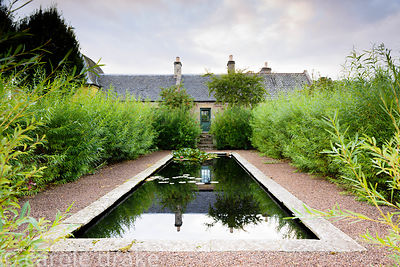 Formal pond surrounded by a willow hedge in the Walled Garden at Broadwoodside, Gifford, East Lothian in September