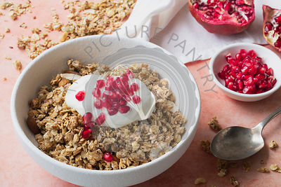 Healthy breakfast bowl of granola, plain yoghurt and pomegranate seeds.