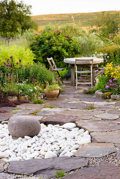 Circular sunken feature of white pebbles in the garden at 2 Durnamuck, Little Loch Broom, Wester Ross in July, with table and...