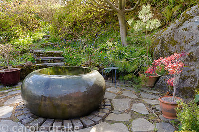 Front garden features a large copper water feature, formerly part of a whisky still, surrounded by lush planting including ac...