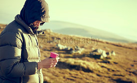 A hiker in a warm down jacket enjoying a hot drink at sunrise on a cold autumn morning while camping on the mountains in the ...