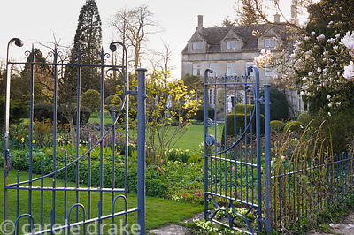 Blue  metal gates and railings separate the pond garden from the main garden behind the house. Barnsley House, Cirencester, G...