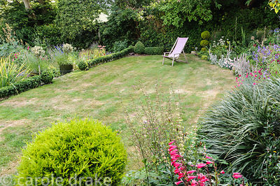 Deckchair on the lawn near the house framed by clipped evergreens and a border full of flowers including penstemons, stachys,...