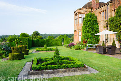 Box parterre on the terrace with yew topiary in the shape of castles complete with flags. Felley Priory, Underwood, Notts, UK