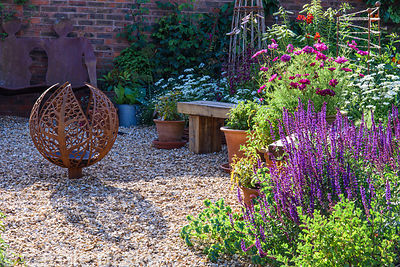 Gravelled area with decorative fire sphere amidst salvias, cosmos, Cerinthe major 'Purpurascens' and Orlaya grandiflora at Ma...