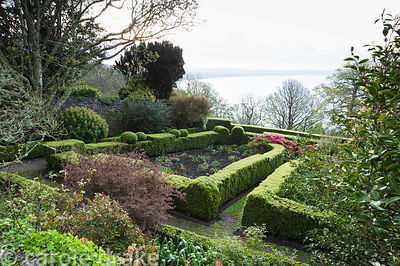 Garden in front of the house contains box edged compartments, and shrubs including bright azaleas, with view across Cardigan ...