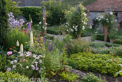 Farmyard garden defined by low box hedging and brick pillars planted with Rosa 'Iceberg' and clematis. Other planting include...