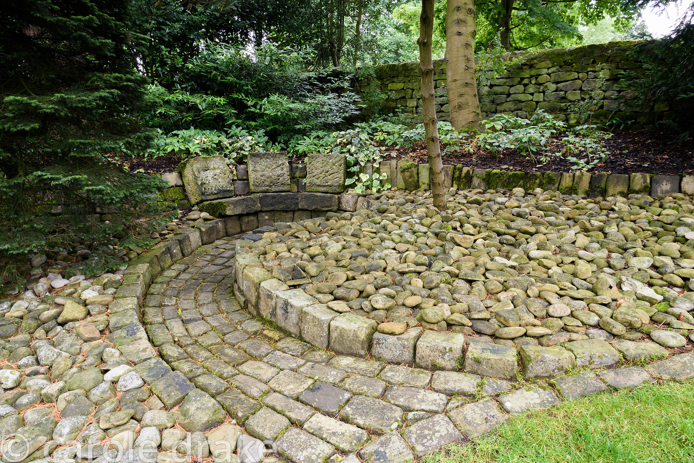 Sunken seating area constructed with stone slabs and framed by ground mulched with large pebbles at York Gate Garden, Adel in...