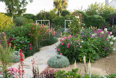Sunken garden has a central stone path that passes between a metal frame supporting climbing roses, with a mass of colourful ...