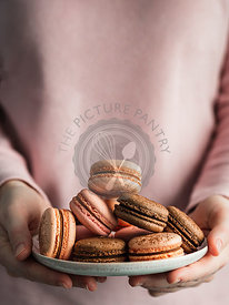 Macarons heap on plate in female hands, vertical