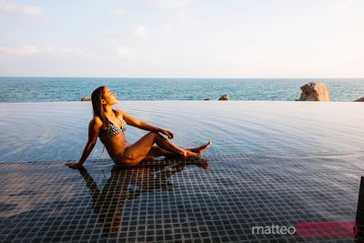 Asian woman sunbathing in an infinity pool, Thailand