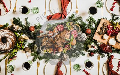 Flat-lay of Christmas table setting with chicken, wine and decorations