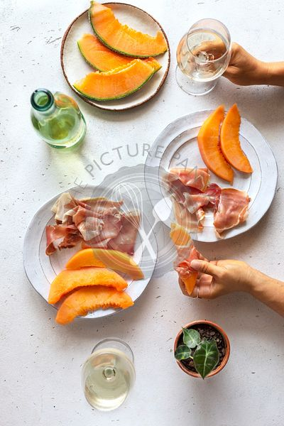 Flat-lay of prosciutto,cantaloupe and white wine  over white table