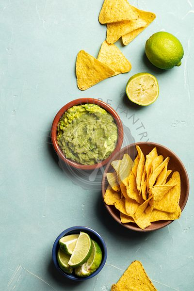Nachos and fresh homemade guacamole on blue background