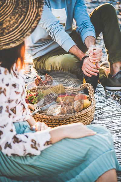 Young couple opening bottle of wine at summer picnic