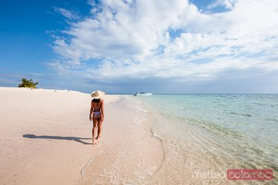 Woman in bikini walking on tropical beach, bamboo island, Thailand