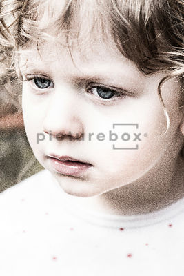 An image of a little girl looking sad.