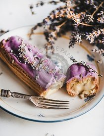 Lavender eclair with cream decorated with flowers and vintage fork