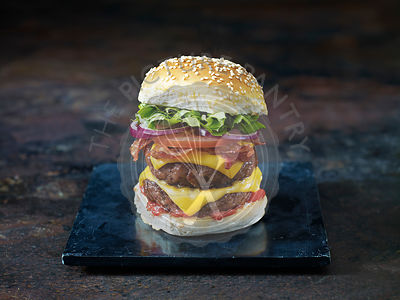 A bacon and double cheese burger against a dark background