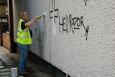 Council workers cleaning off memorial graffiti in Leytonstone after the murder of black teenager Paul Erhahon.